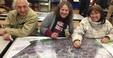 Three residents sit in front of a map at a public meeting on conservation planning.