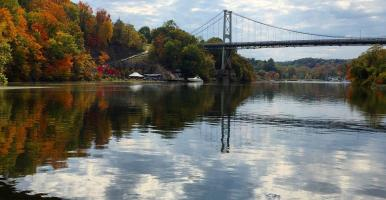 View of Rondout Creek, with clouds reflecting in water and views of Fall foliage and boats. By L Heady